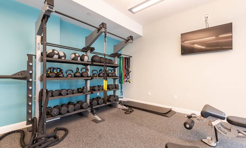 Fitness center at One Wall St in Attleboro with free weights.